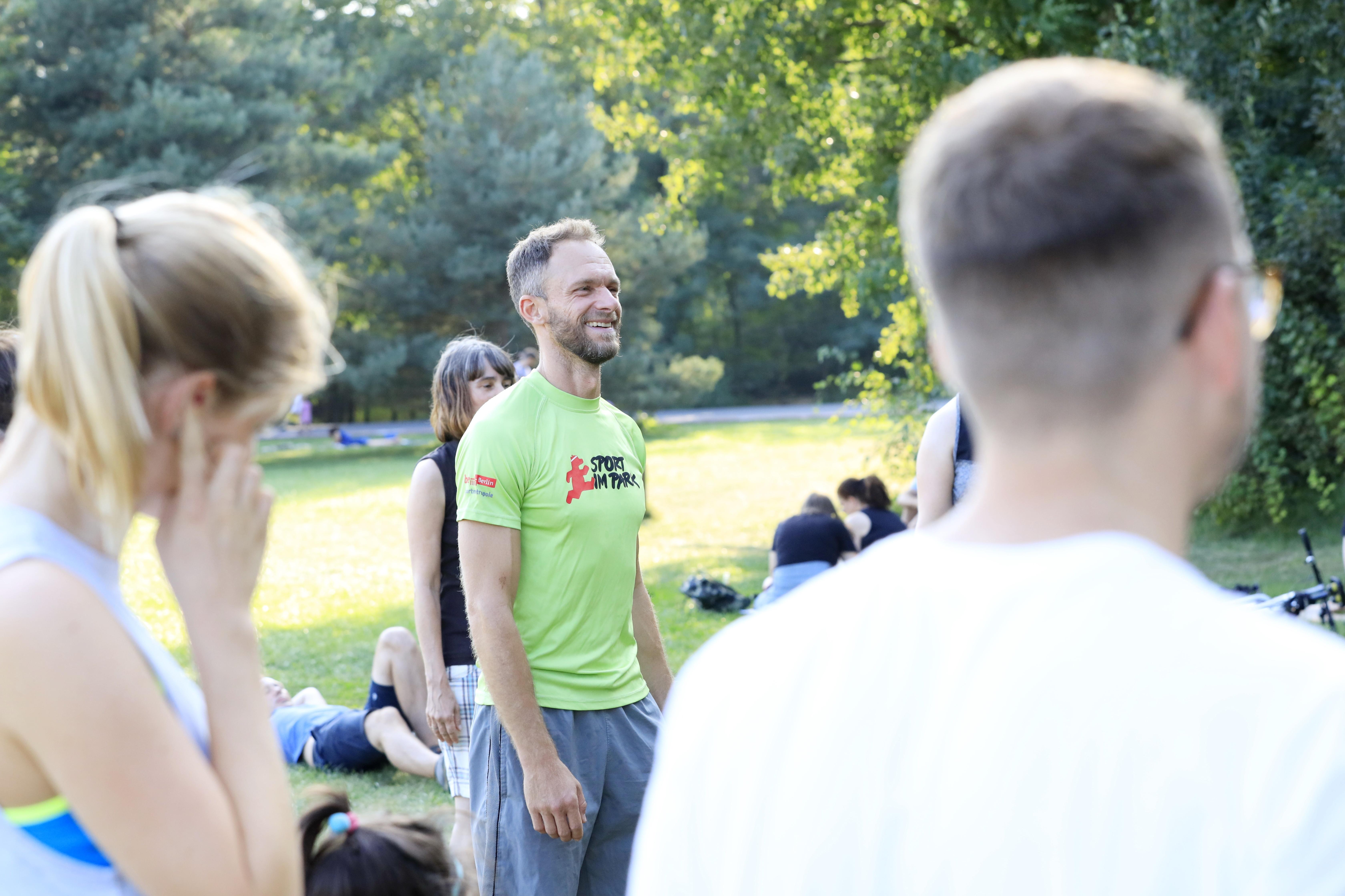 Stadtbewegung Menschen beim Sport im Park mit Trainer